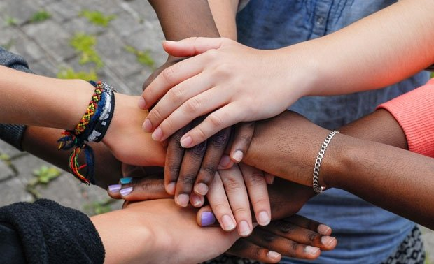 multiracial-teens-stack-hands-teamwork-cooperation